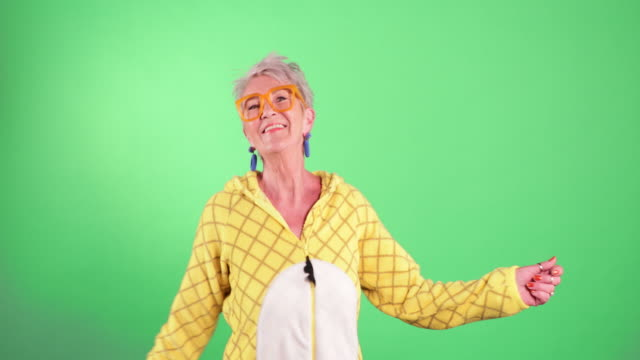 dancing in a onesie - green background stock videos & royalty-free footage