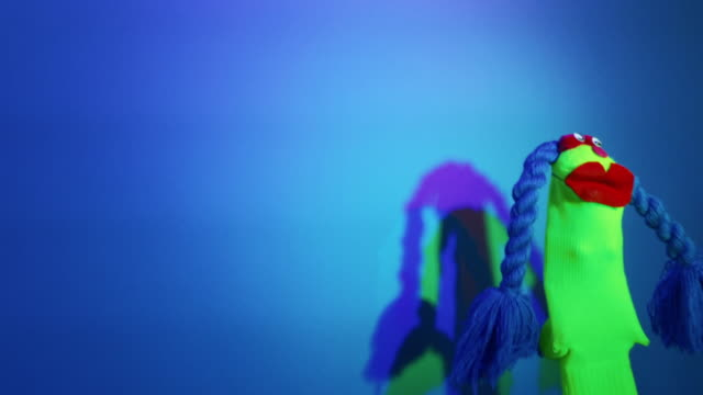 dancing sock puppet with blue braids and red lips - socke stock-videos und b-roll-filmmaterial