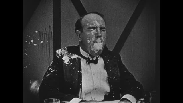1918 dancing waiter (buster keaton) knocks patron, feigning anger to hide guilt before throwing food at customer - colpevolezza video stock e b–roll