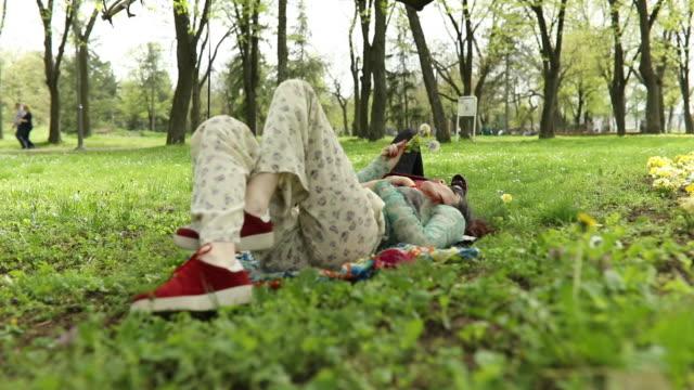vídeos de stock, filmes e b-roll de dente de leão, soprando no parque - cabelo verde