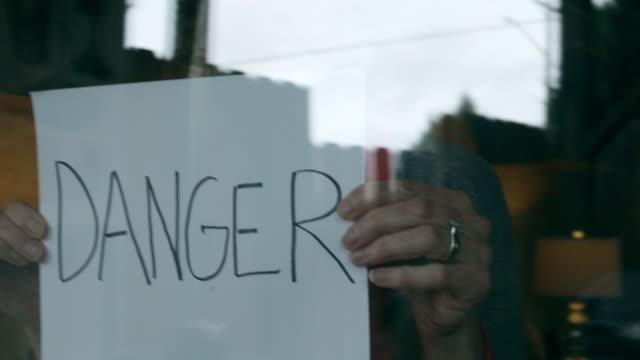 vídeos y material grabado en eventos de stock de peligro durante la crisis de la enfermedad aerotransportada refugio femenino maduro en casa durante la cuarentena de señales de mano 4k serie de videos - epidemiología
