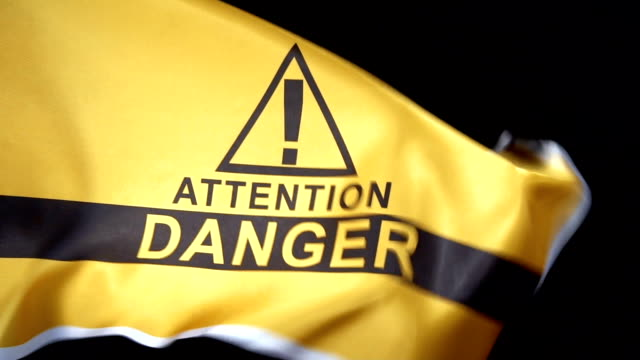 vídeos de stock e filmes b-roll de danger flag waving in dark - ponto de exclamação