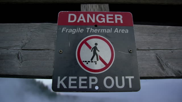"""danger, fragile thermal area, keep out"" sign attached to a wooden barrier next to excelsior geyser crater at dusk/sunset/sunrise/dawn in yellowstone national park in wyoming - keep out sign stock videos & royalty-free footage"