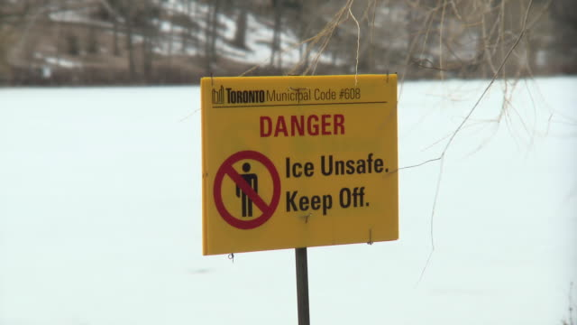 MS RF Danger Ice Unsafe Keep Off sign with frozen lake at high park / Toronto, Ontario, Canada