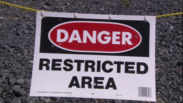 A danger sign hangs in front of a restricted area.