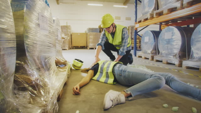 dangerous accident during work. man helping his female colleague. calling for help - caucasian appearance stock videos & royalty-free footage