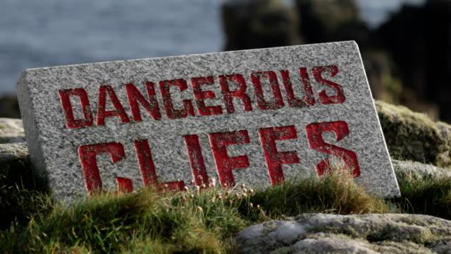 vídeos de stock, filmes e b-roll de perigosos cliffs - sinal de advertência