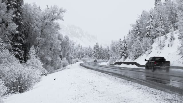 dangerous driving under the snowfall on the highway in mountains in colorado - pick up truck stock videos & royalty-free footage