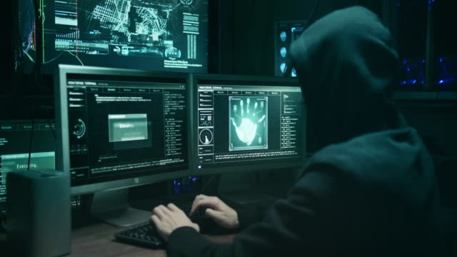vídeos de stock e filmes b-roll de dangerous hooded hacker breaks into government data servers and infects their system with a virus. his hideout place has dark atmosphere, multiple displays, cables everywhere. - criminoso