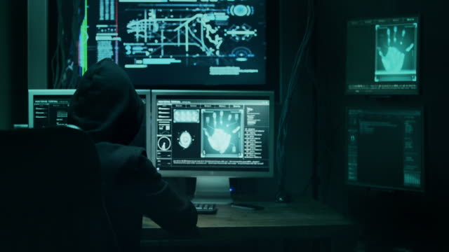 dangerous hooded hacker breaks into government data servers and infects their system with a virus. his hideout place has dark atmosphere, multiple displays, cables everywhere. - war stock videos & royalty-free footage