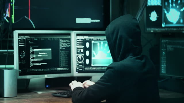 dangerous hooded hacker breaks into government data servers and infects their system with a virus. his hideout place has dark atmosphere, multiple displays, cables everywhere. - hacker stock videos and b-roll footage