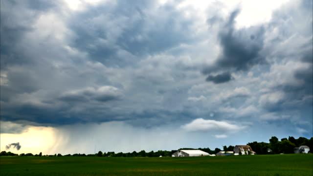 vídeos de stock, filmes e b-roll de nuvens de tempestade perigosas sobre um campo que escorre a chuva - greve
