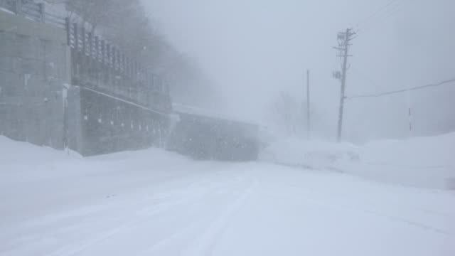 dangerous winter storm and heavy snow hit rural highway in japan - snow storm stock videos and b-roll footage