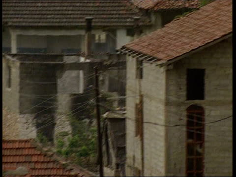 stockvideo's en b-roll-footage met dangers facing returning refugees yugoslavia serbia kosovo ext refugees around water pump houses pan house with no roof soldier next nato flag... - kosovo
