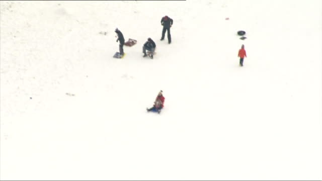 surrey box hill ext people sledging and tobogganing down the hill - サリー州 ボックスヒル点の映像素材/bロール
