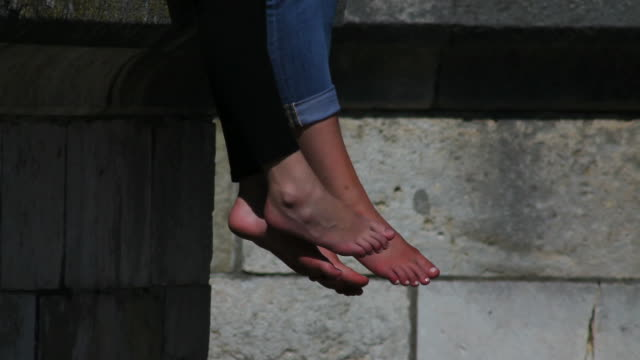 Dangling Feet Of Relaxing Teenage Girls