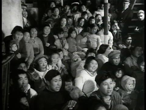 vídeos de stock e filmes b-roll de entertainment danish coast guardsmen sitting w/ inuit eskimo talking ws eskimos watching movie ws theatre screen playing 'dance tonight' humpty... - inuit