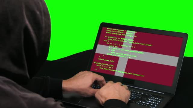vídeos y material grabado en eventos de stock de hacker danés escribiendo código hacking en su ordenador portátil con la bandera danesa en el fondo de la pantalla verde - danish flag