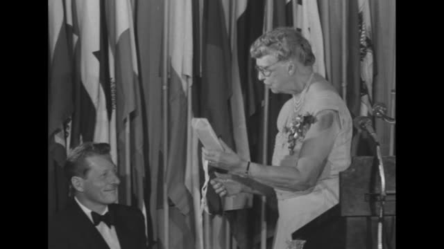 Danny Kaye and Eleanor Roosevelt stand behind head table prior to ceremony at dinner at WaldorfAstoria Hotel chatting with others on dais Kaye speaks...