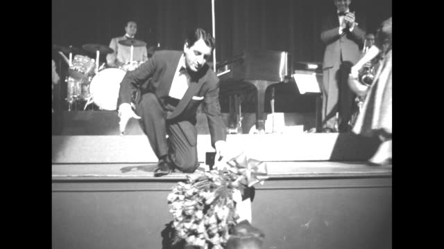 danny thomas, on paramount theatre stage in front of orchestra and band leader carmen cavallero, parts hands with peggy lee as she bows off stage,... - warner bros stock videos & royalty-free footage