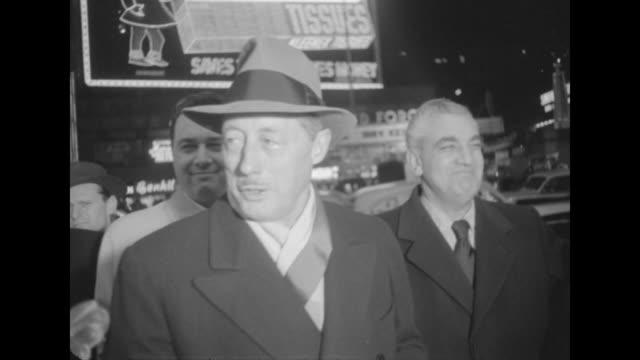 MS of Danton Walker on sidewalk outside NYC movie premiere of The Eddie Cantor Story