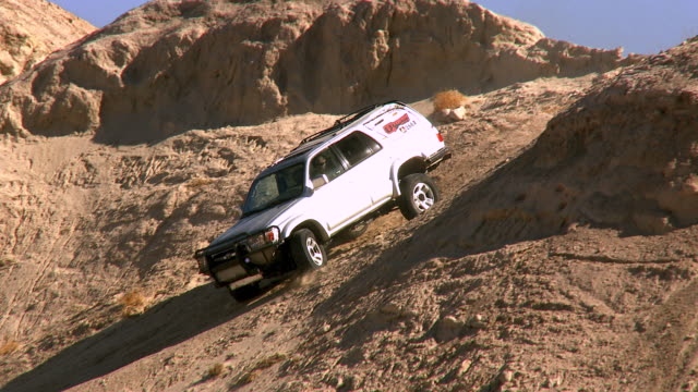 WS TD PAN ZO Daredevil driver SUV moving down steep incline of barren dirt hill in desert / Salton City, California, USA