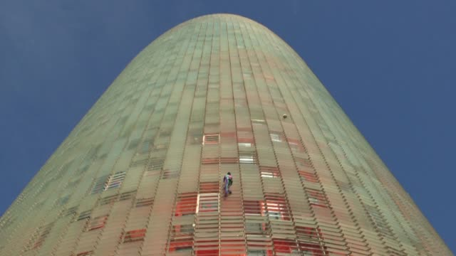 daredevil french climber alain robert scales one of the tallest skyscrapers in barcelona without a harness before being arrested - briglia video stock e b–roll