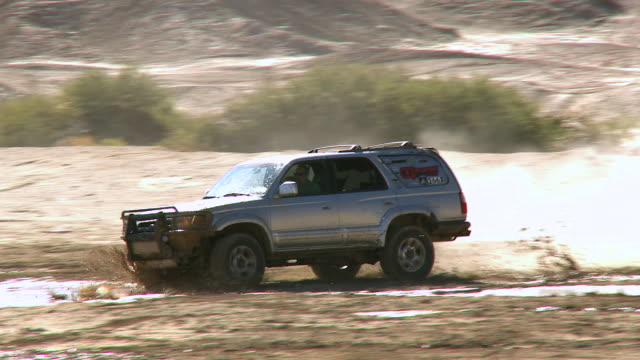 ws pan daredevil suv plows his vehicle through deep mud spraying lots of  muddy water / salton city, california, usa - steep stock videos and b-roll footage