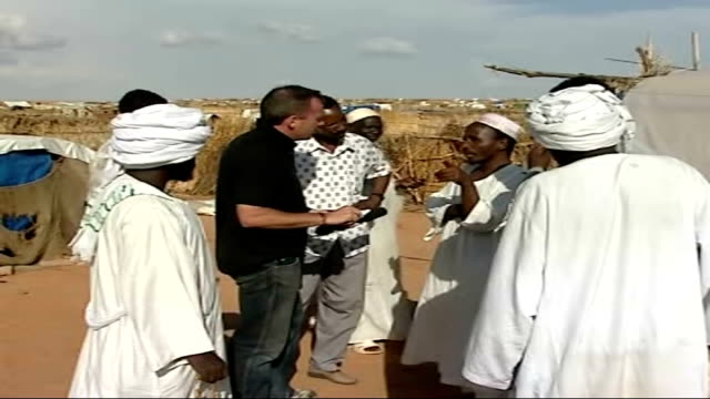 darfur crisis continues; male refugee being interviewed female refugee in bright green robes sitting with group of women and talking to reporter... - sexual violence stock videos & royalty-free footage