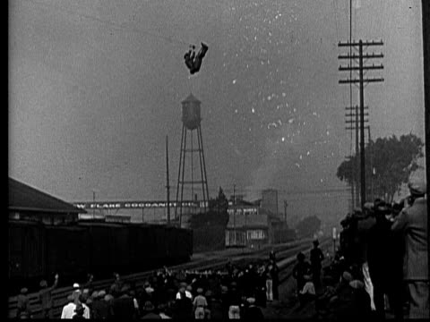 ws, cu, b&w, daring police officer escaping from burning building using wire, jumping onto safety sheet, 1920's  - high up stock videos & royalty-free footage