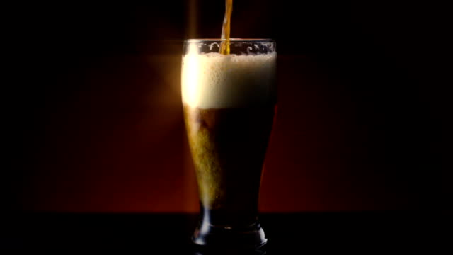 dark amber beer in pilsner glass star filter - 茶色背景点の映像素材/bロール