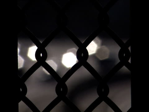 dark chain-link fence with spots of light (diffused reflections from cars) travelling through shot from right to left - travelling light stock videos & royalty-free footage