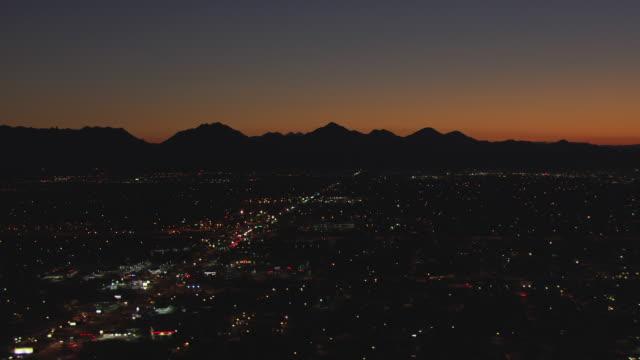 ws aerial dark city and sun light on horizon behind mountains / phoenix, arizona, united states  - twilight stock videos & royalty-free footage