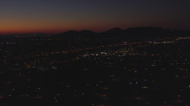 ws aerial dark city and sun light on horizon / phoenix, arizona, united states  - arizona stock videos & royalty-free footage