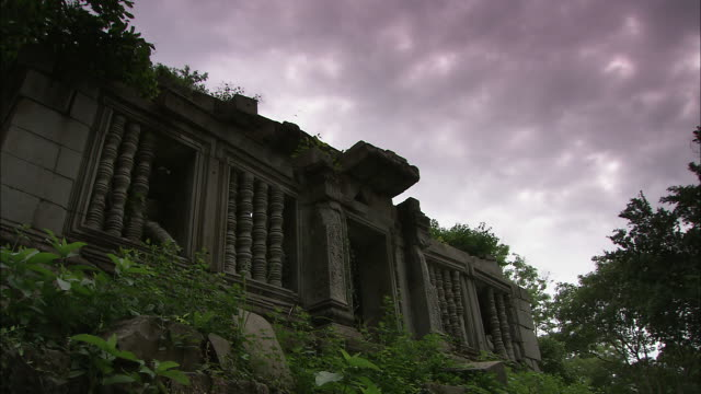 a dark cloud bank drifts over a temple. - 生い茂る点の映像素材/bロール