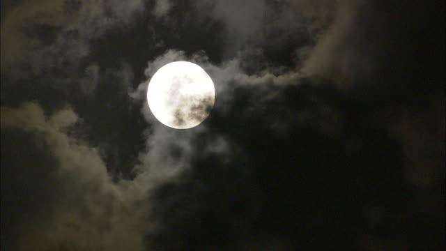 dark clouds drift across a full moon. - vollmond stock-videos und b-roll-filmmaterial