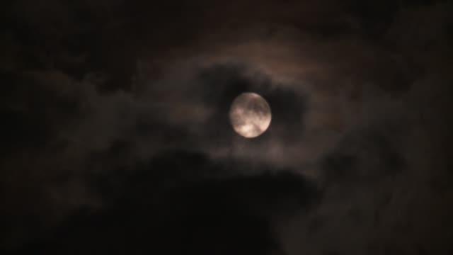 dark clouds drift across the night sky. - moon stock videos & royalty-free footage