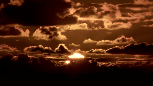 vidéos et rushes de dark clouds drift past a brilliant setting sun. - coucher de soleil