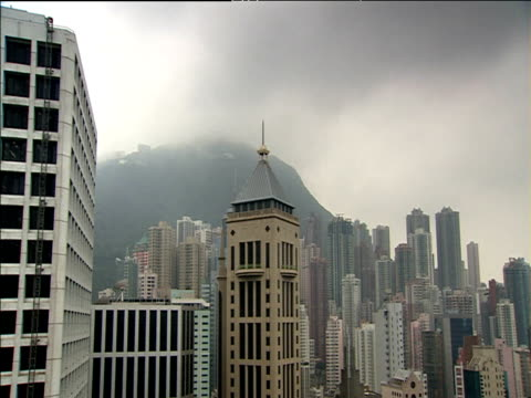 Dark clouds float above skyscrapers Victoria Peak in background Hong Kong