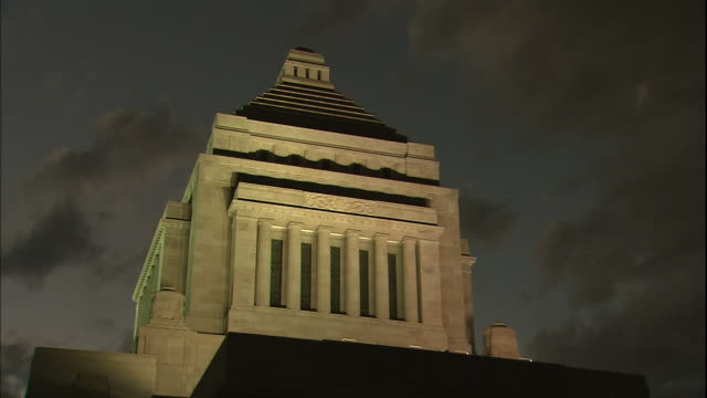 dark clouds gather over the illuminated national diet building in tokyo. - 国会議事堂点の映像素材/bロール