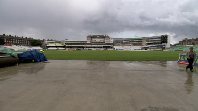 stockvideo's en b-roll-footage met dark clouds hang over the oval cricket ground on a wet day. available in hd. - cricketveld
