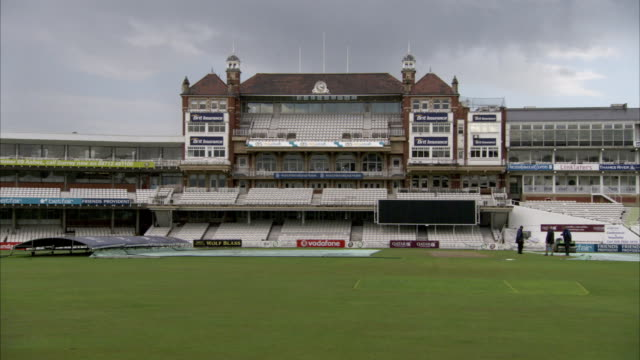 dark clouds hang over the pavilion as groundskeepers work on the field at the oval cricket ground. available in hd. - グランドキーパー点の映像素材/bロール