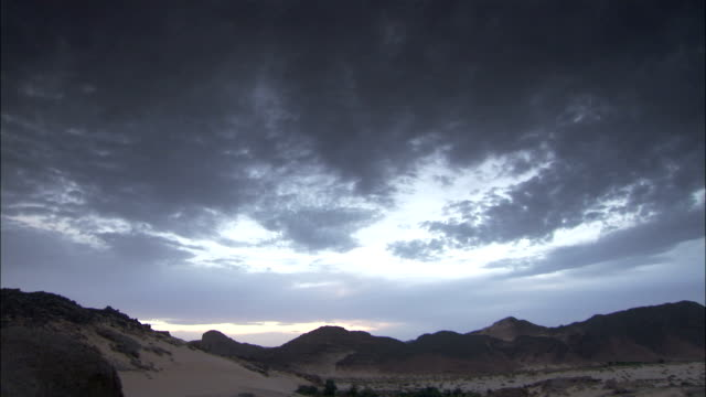 Dark clouds hover over rocky landscape Djanet Algeria Available in HD.