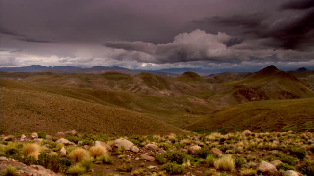 Dark clouds hover over rolling hills. Available in HD.