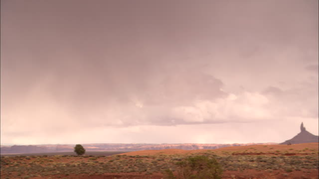 vidéos et rushes de dark clouds loom over the rock spires in monument valley. - monument valley