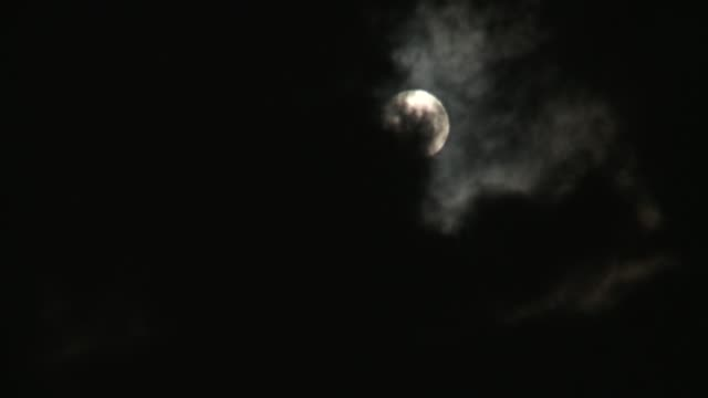 dark clouds move across the sky and reveal a full moon before blocking it out again. - vollmond stock-videos und b-roll-filmmaterial