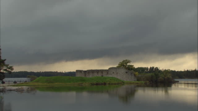 t/l ws dark clouds moving quickly over ruins of old castle on island in lake / vaxjo, sweden - vaxjo stock videos & royalty-free footage