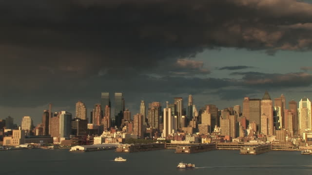 dark clouds over the skyline of the upper west side in manhattan at sunset showing boats passing on the hudson river - upper west side manhattan stock videos and b-roll footage