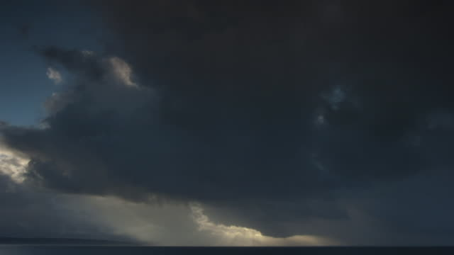 Dark clouds pass over ocean.
