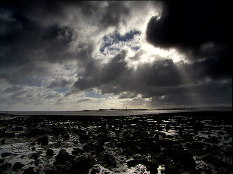 dark clouds roll above muddy beach and waters towards island of lindisfarne northumberland - northumberland coast stock videos & royalty-free footage